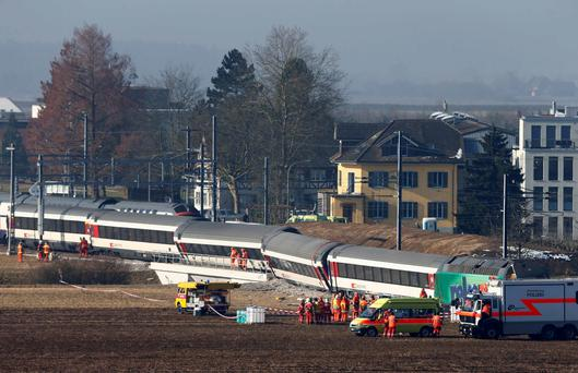 Rescue workers stand next to a derailed train after two trains collided near Rafz around 30 km (18 miles) from Zurich February 20, 2015. Two passenger trains collided in Switzerland on Friday, causing five injuries and disrupting commuter routes into Zurich, police and rail operator SBB said.