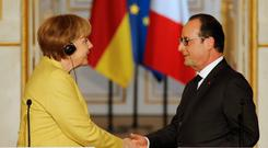 German Chancellor Angela Merkel and French President Francois Hollande pledged to uphold the sanctity of the euro