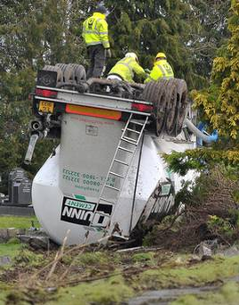 Driver escapes as cement lorry overturns and crashes into graveyard. Pic Belfast Telegraph