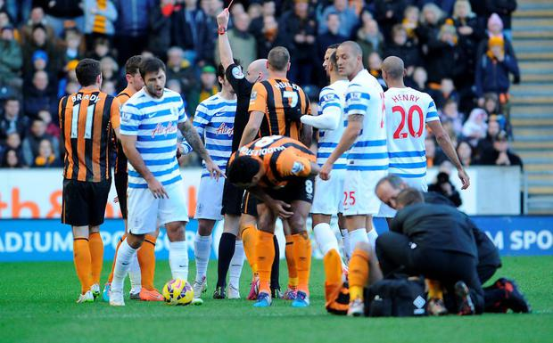 Referee Mr Anthony Taylor sends off QPR's Joey Barton during the Barclays Premier League match at the KC Stadium, Hull.