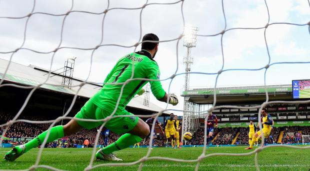 Santi Cazorla scores from the penalty spot past goalkeeper Julian Speroni of Crystal Palace.
