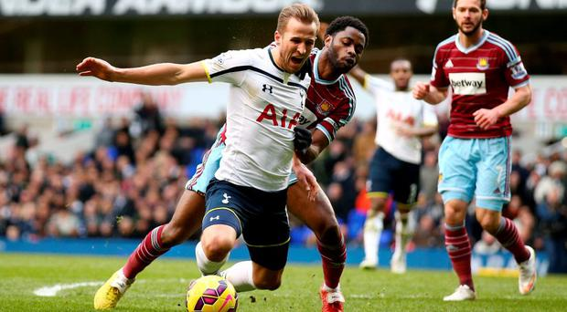 Harry Kane goes down under the challenge from Alex Song of West Ham to win an injury time penalty.