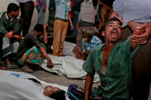 Bangladeshi relatives wail near bodies of victims after a river ferry carrying about 100 passengers capsized Sunday after being hit by a cargo vessel,in Manikganj district, about 40 kilometers (25 miles) northwest of Dhaka, Bangladesh, Sunday, Feb. 22, 2015. (AP Photo/ A.M. Ahad)