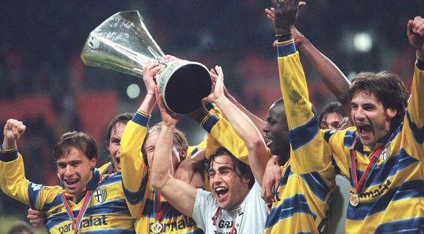 Captain Fabio Cannavaro holds the trophy as Parma players celebrate winning the UEFA Cup in 1999. Photo: Alexander Hassenstein/Bongarts/Getty Images