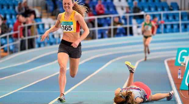 Claire Tarplee (Dundrum South Dublin AC) falls as eventual winner Kerry O'Flaherty (Newcastle and District AC) races for the line in the Women's 1,500m final of the GloHealth Senior Indoor Championships in AIT