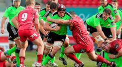 Munster's Tommy O'Donnell is tackled by Ken Owens of the Scarlets during their Guinness Pro12 clash at Parc Y Scarlets. Photo: Steve Pope / SPORTSFILE