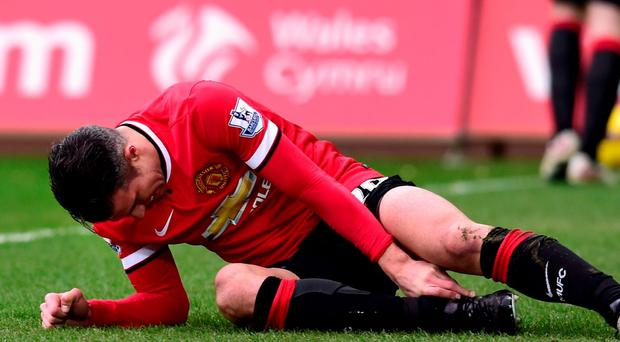 Manchester United striker Robin Van Persie holds his leg after picking up an injury which left him in crutches during the Premier League clash with Swansea City at the Liberty Stadium. Photo: Stu Forster/Getty Images