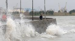 A walker dodges tall waves at Sandymount strand in Dublin yesterday. Photo: Justin Farrelly.