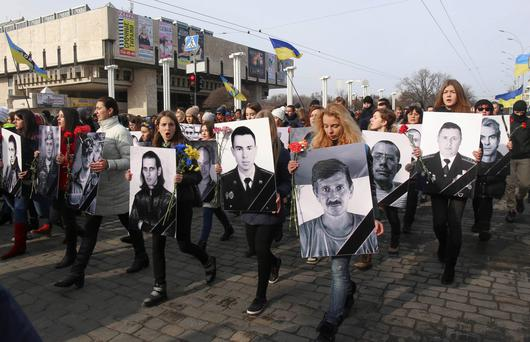 People carry portraits of local residents killed in fighting with pro-Russian separatists during a commemoration rally in Kharkiv, where at least two people were killed when a blast struck the crowd (REUTERS/Stringer)