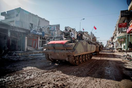 Turkish army vehicles drive in a street of the Syrian town of Kobane during an operation to relieve the garrison guarding the Suleyman Shah mausoleum in northern Syria (Getty Images)