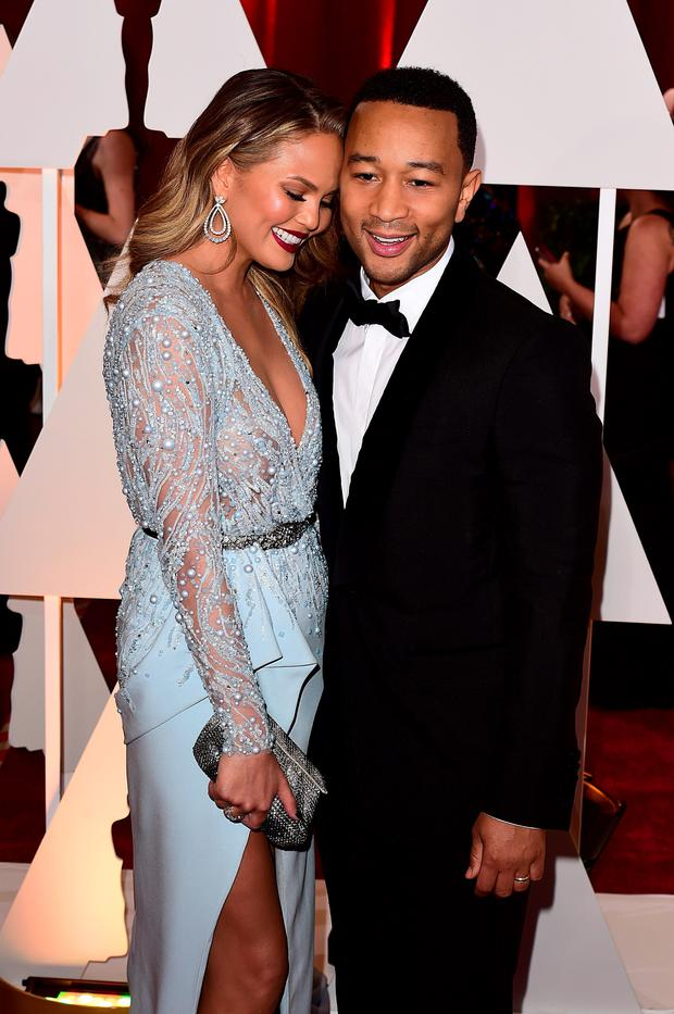 Chrissy Teigen and John Legend arriving at the 87th Academy Awards held at the Dolby Theatre in Hollywood, Los Angeles, USA. PRESS ASSOCIATION Photo. Picture date: Sunday February 22, 2015. See PA story SHOWBIZ Oscars. Photo credit should read: Ian West/PA Wire