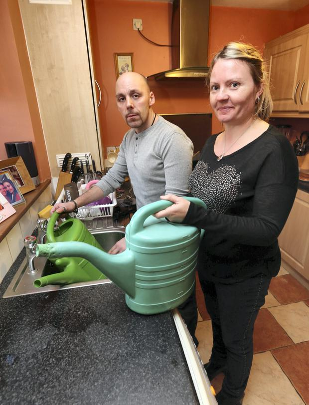 Adriano Prete and his wife Lisa Gibbons Prete pictured filling containers with water to fill the attic tank at their Finglas home. The water pressure is so low it won't reach the attic tank