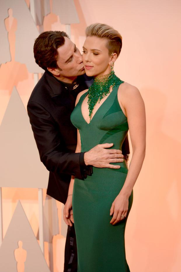 Actor John Travolta (L) and actress Scarlett Johansson attend the 87th Annual Academy Awards