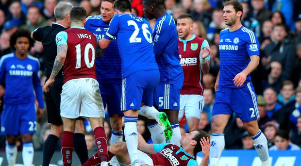 Referee Martin Atkinson shows the red card to Nemanja Matic of Chelsea for his reaction to the tackle by Ashley Barnes of Burnley during the Barclays Premier League match between Chelsea and Burnley at Stamford Bridge