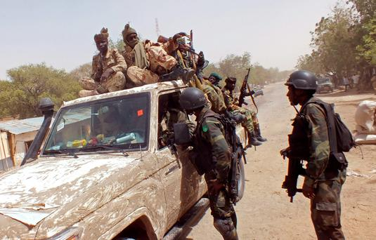 Chadian soldiers on top of a truck, left, speak to Cameroon soldiers, right, standing next to the truck, on the border between Cameroon and Nigeria as they form part of the force to combat regional Islamic extremists force's including Boko Haram, near the town of Gambarou, Nigeria (AP Photo/Edwin Kindzeka Moki)