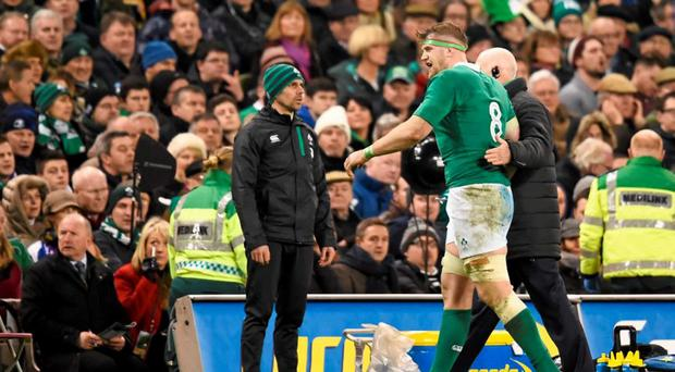 Jamie Heaslip is helped off the field after being kneed in the back by Pascal Pape