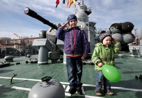 Children salute onboard a Russian warship during celebrations for the Defender of the Fatherland Day in Sevastopol, Crimea (REUTERS/Pavel Rebrov)