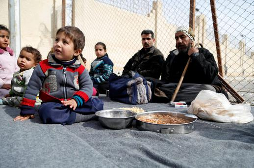 Displaced civilians who were evacuated from rebel-controlled areas of eastern Ghouta, sit at a temporary shelter in the Damascus suburb of Qudsaya, a government-controlled area (REUTERS/Omar Sanadiki)