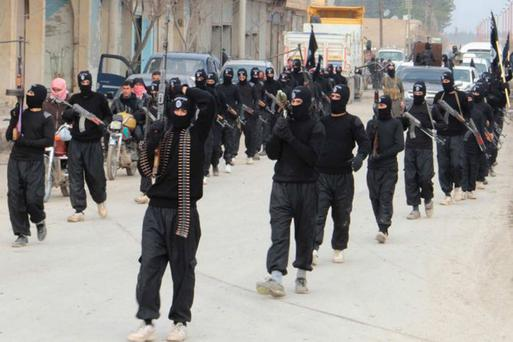 Isis militants marching through a Syrian town