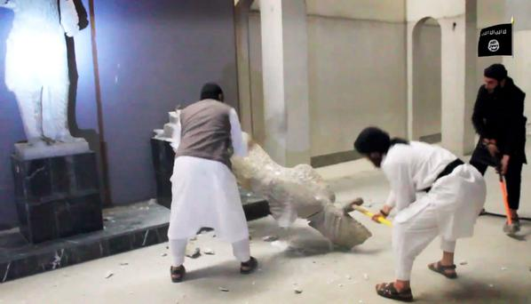 In this image made from video posted on a social media account affiliated with the Islamic State group on Thursday, Feb. 26, 2015, which has been verified and is consistent with other AP reporting, militants take sledgehammers to an ancient artifact in the Ninevah Museum in Mosul, Iraq. AP Photo via militant social media account