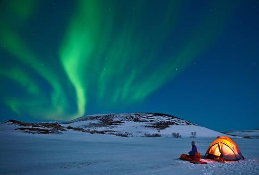 Woman outside tent with Northern lights, Myvatn, Iceland