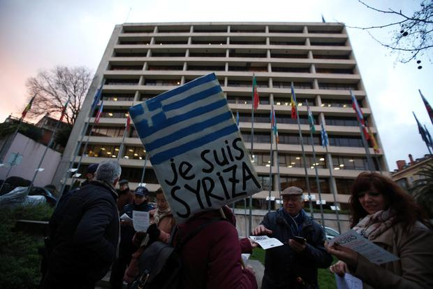 A woman holds a placard during a vigil to support the newly elected Greek government, outside the European Commission headquarters in Lisbon. Photo: Reuters