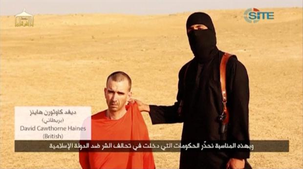 A masked, black-clad militant, who has been identified by the Washington Post newspaper as a Briton named Mohammed Emwazi, stands next to a man purported to be David Haines in this still image from a video obtained from SITE Intel Group website February 26, 2015