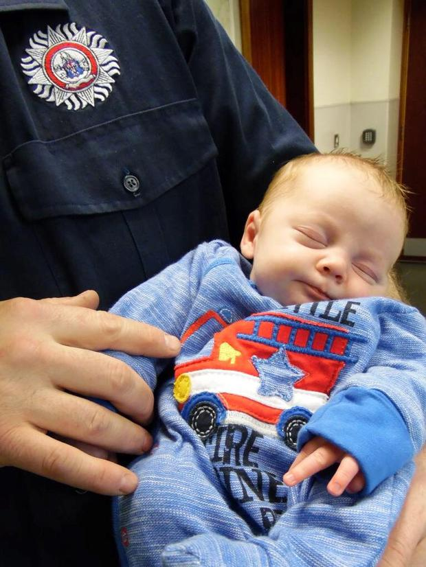 Baby Bobby Doyle visits firemen at Tallaght two weeks after he was delivered at home.