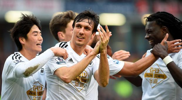 Swansea City's Jack Cork (centre) celebrates their first goal during the Barclays Premier League match at Turf Moor