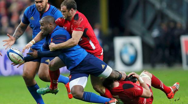 France's Eddy Ben Arous (L) attempts to evade the tackle of Wales' Jamie Roberts (C) and Alun Wyn Jones (R) during their Six Nations rugby union match at the Stade de France stadium