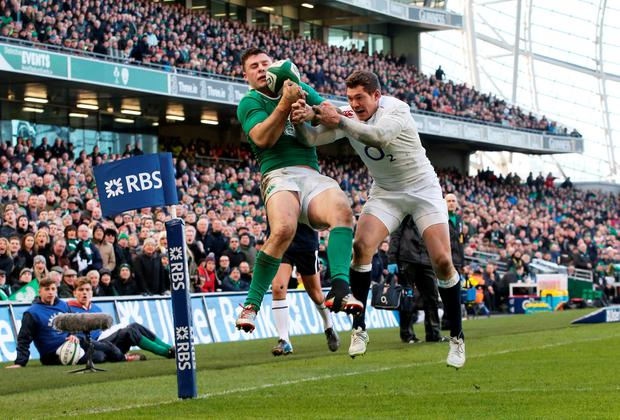 Robbie Henshaw of Ireland takes a high ball to score the opening try despite the efforts of Alex Goode of England during the RBS Six Nations match between Ireland and England at the Aviva Stadium on March 1, 2015 in Dublin, Ireland
