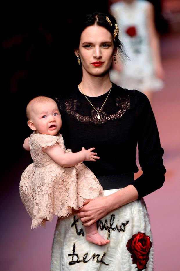 A model holds a baby as she presents a creation for fashion house Dolce & Gabbana at the women Fall / Winter 2015/16 Milan's Fashion Week
