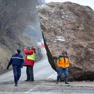 A Gendarme (L) and a Red Cross rescuer (R) stand near a huge rock that fell on February 27 onto the RD117 road leading to the ski resorts of Moutiers, Les Menuires and Val Thorens in the Tarentaise valley
