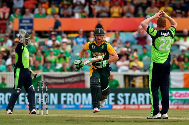 South Africa's AB de Villiers (C) runs after hitting a ball off Ireland's bowler Kevin O'Brien (R) as wicketkeeper Gary Wilson (L) looks on, during the 2015 Cricket World Cup Pool B match between Ireland and South Africa in Canberra on March 3, 2015. AFP PHOTO / Peter PARKS --IMAGE RESTRICTED TO EDITORIAL USE - STRICTLY NO COMMERCIAL USE--PETER PARKS/AFP/Getty Images