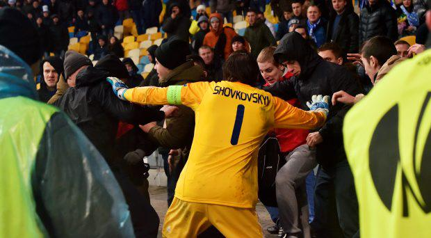 Dynamo Kiev's goalkeeper Oleksandr Shovkovskiy tries to prevent his supporters from fighting with security guards during the UEFA Europa League round of 32 second-leg football match FC Dynamo and EA Guingamp in Kiev on February 26, 2015