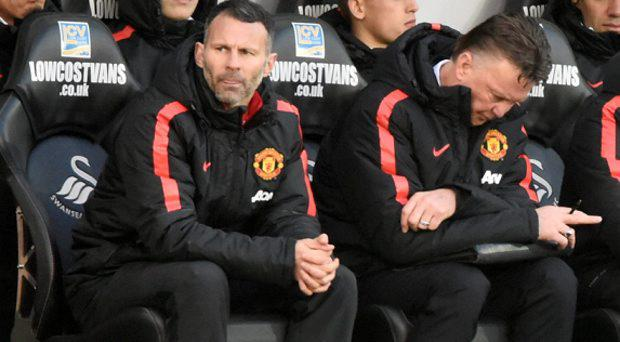 Manchester United manager Louis van Gaal looks dejected with his assistant Ryan Giggs