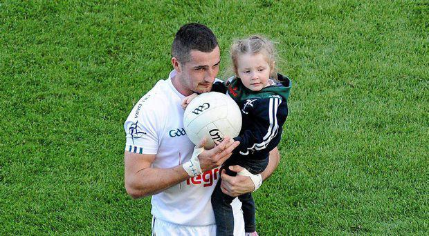 Kildare's Aindria Mac Lochlainn leaves the pitch after the game with his daughter Ella May