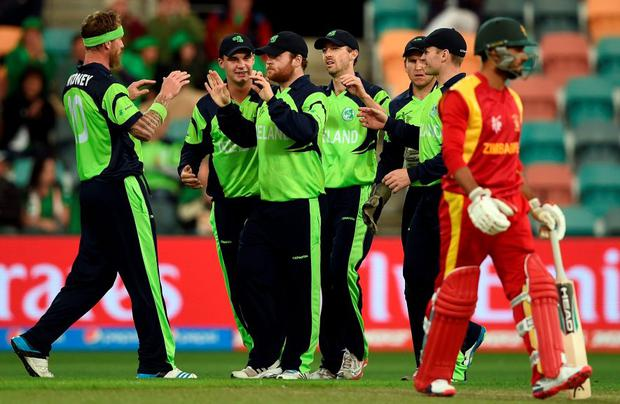 Ireland cricketers celebrate the wicket of Zimbabwe batsman Sikandar Raza (R) at the Bellerive Oval ground during the 2015 Cricket World Cup Pool B match.