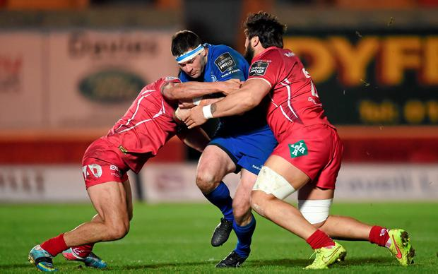 Fergus McFadden, Leinster, is tackled by Regan King, left, and Rory Pitman, Scarlets