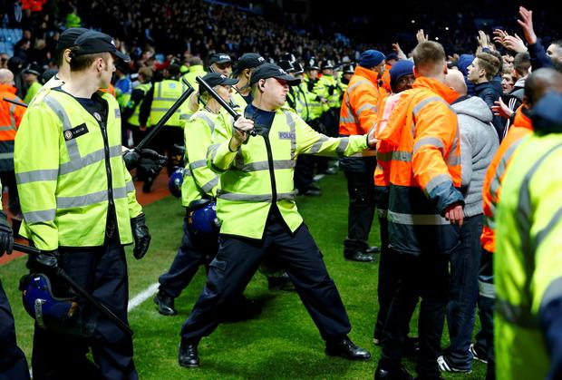 Police clash with fans on the pitch at full time