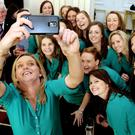President Higgins hosts an event at the Aras to mark International Women's Day ...Pic shows Kate Dillon a member of the Irish Hockey Team as she takes a group photo of herself and team mates in the the Aras during the reception