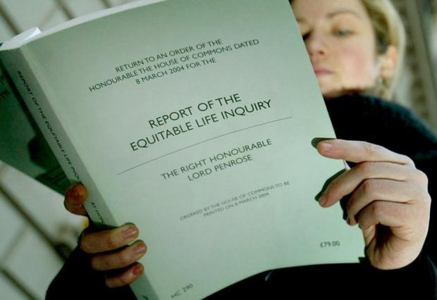 A woman reads a report into the collapse of Equitable Life. Picture: Reuters