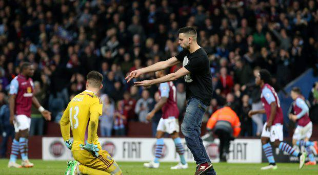 An Aston Villa fan gestures towards West Brom's Boaz Myhill as he celebrates their second goal on the pitch