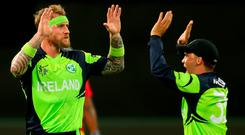 HOBART, AUSTRALIA - MARCH 07: John Mooney of Ireland is congratulated by team mates after getting the wicket of Sikandar Raza of Zimbabwe during the 2015 ICC Cricket World Cup match between Zimbabwe and Ireland at Bellerive Oval on March 7, 2015 in Hobart, Australia. (Photo by Quinn Rooney/Getty Images)