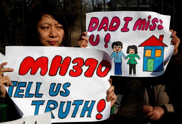 Catherine Gang, whose husband Li Zhi was onboard the missing Malaysia Airlines flight MH370, holds a sign during a gathering of family members of the missing passengers outside the Malaysian embassy in Beijing March 8, 2015. Malaysian and Chinese officials say they are committed to the search for MH370 and in assisting families who are still waiting for concrete information on what happened to their loved ones a year ago. REUTERS/Kim Kyung-Hoon (CHINA - Tags: TRANSPORT DISASTER)