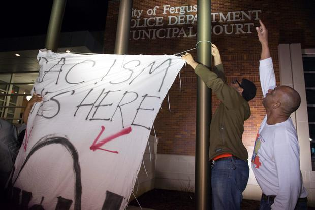 Protesters hang up a flag which reads,