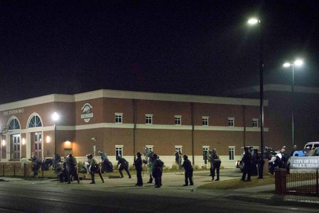 Police stand guard moments after gun shots were fired outside the City of Ferguson Police Department and Municipal Court in Ferguson, Missouri REUTERS/Kate Munsch