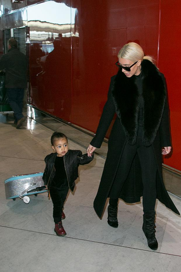 Kim Kardashian West and her daughter North West are seen at 'Charles-de-Gaulle' airport on March 12, 2015 in Paris, France. (Photo by Marc Piasecki/GC Images)