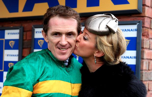 Tony McCoy (left) receives a kiss from wife Chanelle McCoy after winning the Ryanair Chase on Uxizandre during the Cheltenham Festival at Cheltenham Racecourse