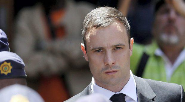 Oscar Pistorius is escorted by police officers as he leaves the high court in Pretoria, South Africa